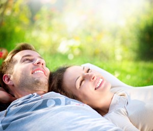 Happy Smiling Couple Relaxing on Green Grass.Park.Young Couple L